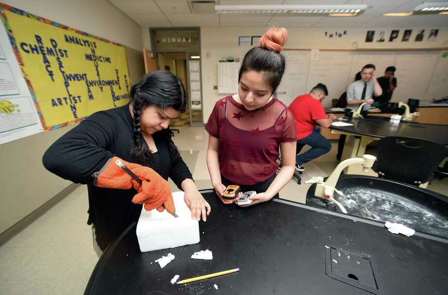 Cynthia Sanchez, left, 16, and Julia Alvarez, 17, carve out a foam block to fit a camera and GPS for a weather baloon at Metropolitan Business Academy in New Haven. Photo: Arnold Gold / Hearst Connecticut Media / New Haven Register