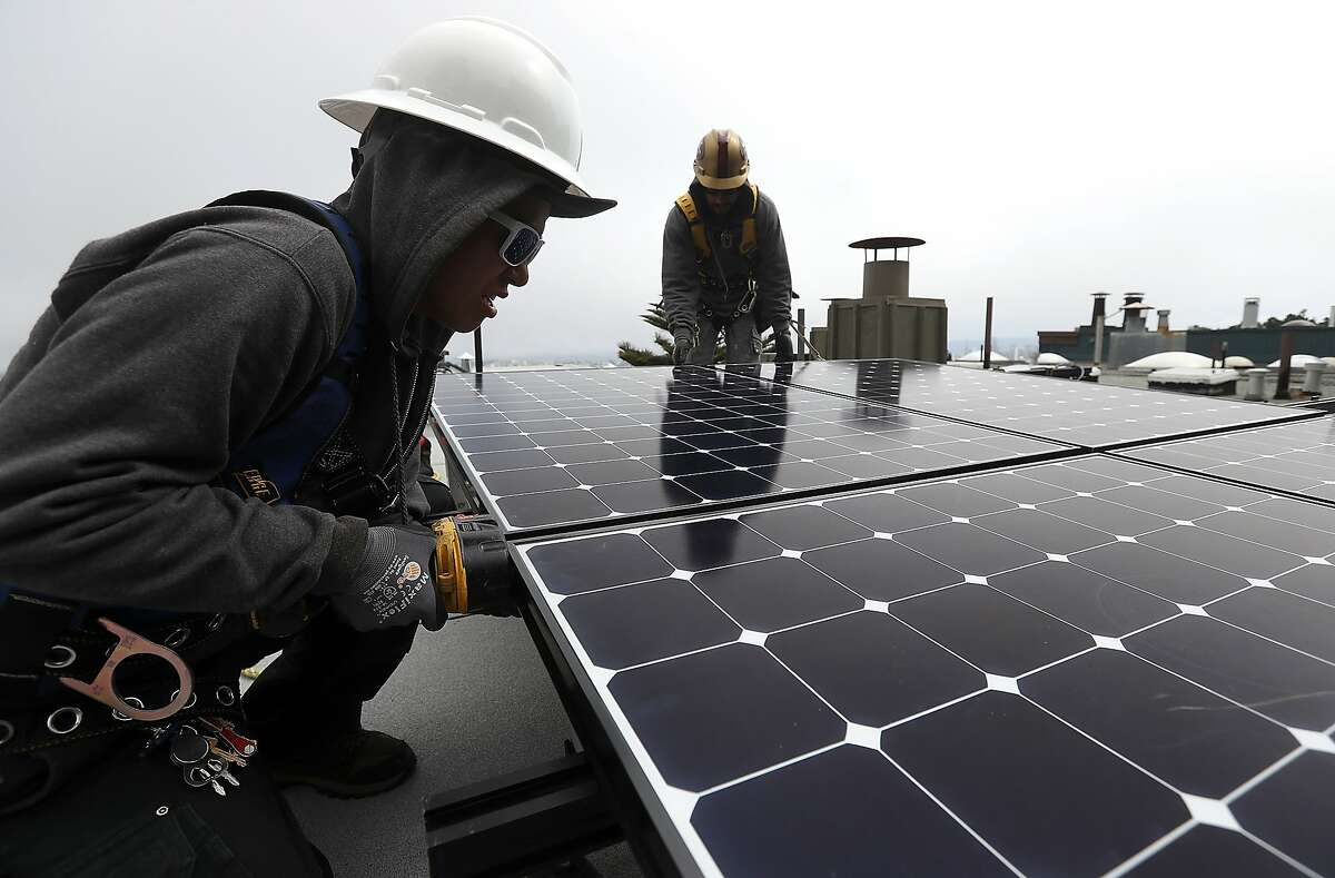 Luminalt solar installers Pam Quan (L) and Walter Morales (R) install solar panels on the roof of a home on May 9, 2018 in San Francisco.