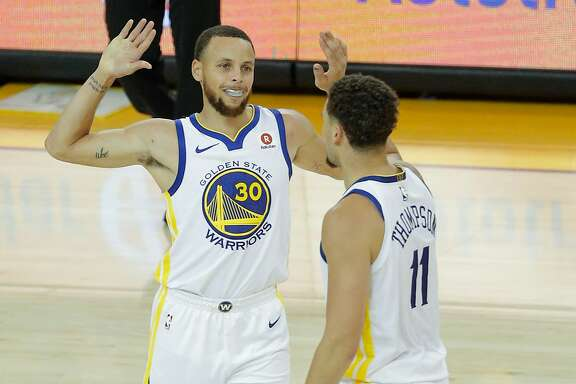 Golden State Warriors' Stephen Curry and Klay Thompson high five after Curry hit a three-pointer in the third quarter during game 5 of the Western Conference Semifinals between the Golden State Warriors and the New Orleans Pelicans at Oracle Arena on Tuesday, May 8, 2018 in Oakland, Calif.