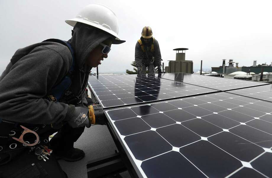 SAN FRANCISCO, CA - MAY 09:  Luminalt solar installers Pam Quan (L) and Walter Morales (R) install solar panels on the roof of a home on May 9, 2018 in San Francisco, California. The California Energy Commission is set to vote on proposed legislation that would require all new homes in the state of California to have solor panels. If passed, the new mandate would require the panels on new homes up to three stories tall and is estimated to cost nearly $10K per home.  (Photo by Justin Sullivan/Getty Images) Photo: Justin Sullivan, Staff / Getty Images / 2018 Getty Images