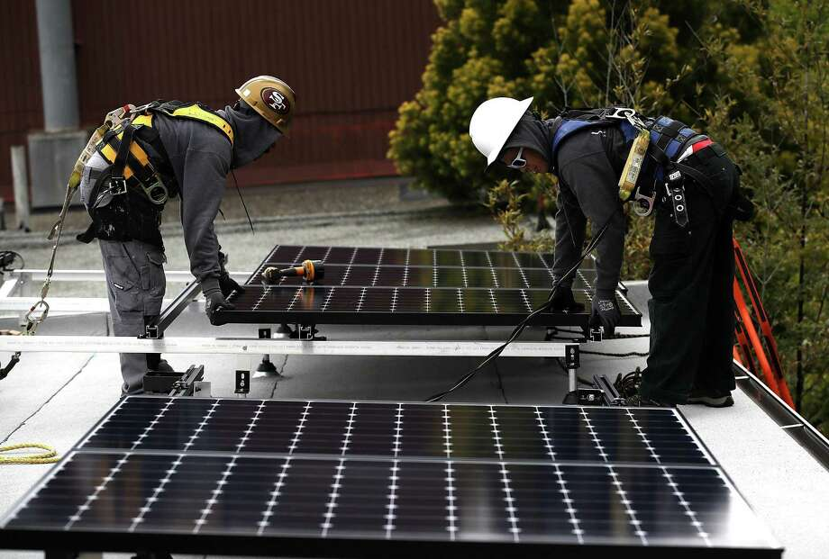 SAN FRANCISCO, CA - MAY 09:  Luminalt solar installers Pam Quan (R) and Walter Morales (L) install solar panels on the roof of a home on May 9, 2018 in San Francisco, California. The California Energy Commission is set to vote on proposed legislation that would require all new homes in the state of California to have solor panels. If passed, the new mandate would require the panels on new homes up to three stories tall and is estimated to cost nearly $10K per home.  (Photo by Justin Sullivan/Getty Images) Photo: Justin Sullivan, Staff / Getty Images / 2018 Getty Images