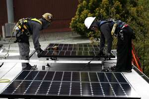 SAN FRANCISCO, CA - MAY 09:  Luminalt solar installers Pam Quan (R) and Walter Morales (L) install solar panels on the roof of a home on May 9, 2018 in San Francisco, California. The California Energy Commission is set to vote on proposed legislation that would require all new homes in the state of California to have solor panels. If passed, the new mandate would require the panels on new homes up to three stories tall and is estimated to cost nearly $10K per home.  (Photo by Justin Sullivan/Getty Images)