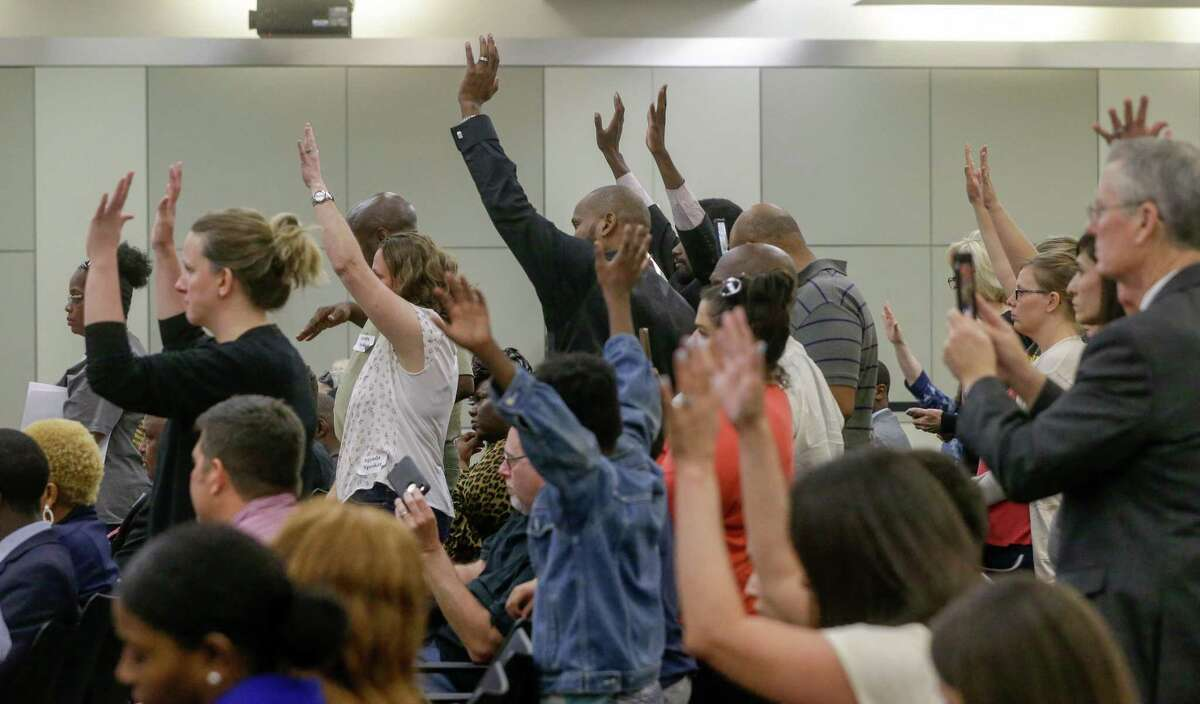 People wave their hands in response to a speaker during the Houston ISD board meeting Tuesday, April 24, 2018. The trustees were scheduled to vote on whether to hand over control of 10 chronically low-performing schools to Energized For STEM Academy, which already runs four in-district HISD charters. Many of the large crowd attending the meeting are against the partnership. ( Melissa Phillip / Houston Chronicle )