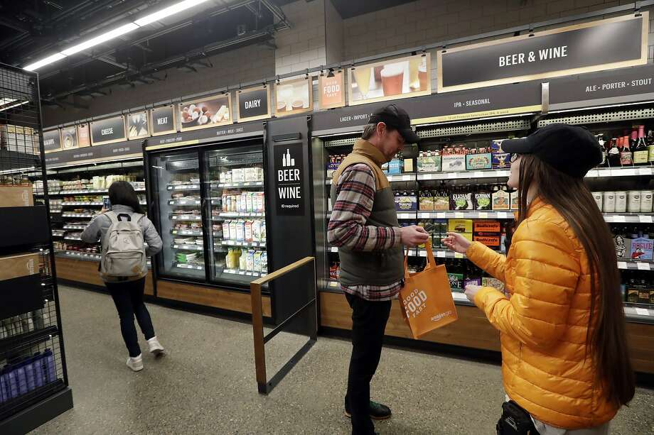 An Amazon Go employee (right) checks the ID of a shopper in the wine and beer section of the store in Seattle. San Francisco might be getting its own Amazon Go store. Photo: Photos By Elaine Thompson / Associated Press