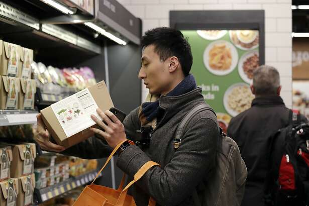 FILE- In this Jan. 22, 2018, file photo, customer Paul Fan shops at an Amazon Go store in Seattle. On Tuesday, March 18, 2018, the Labor Department reports on U.S. consumer prices for February. (AP Photo/Elaine Thompson, File)