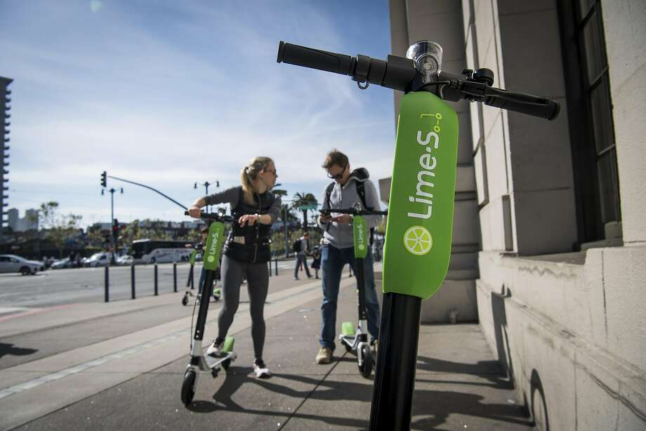 People use a smartphone to unlock Neutron Holdings Inc. LimeBike shared electric scooters on the Embarcadero in San Francisco, California, U.S., on Thursday, May 3, 2018.  Photo: David Paul Morris / Bloomberg