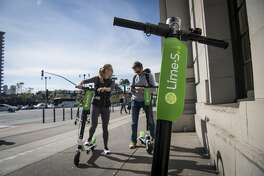 People use a smartphone to unlock Neutron Holdings Inc. LimeBike shared electric scooters on the Embarcadero in San Francisco, California, U.S., on Thursday, May 3, 2018. City officials, eager to do something about the electric scooters issue, are sending cease-and-desist letters and are planning to require permits soon, while impounding any that they say are parked illegally. Photographer: David Paul Morris/Bloomberg