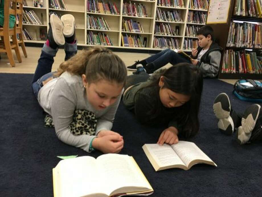 Students at Sequoia Elementary School in Oakland read in the school library. The Oakland Unified School District says 24 of its 84 libraries are closed, more than one-fourth of them. Photo: Friends Of The Oakland Public School Libraries