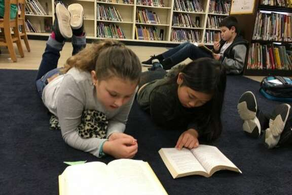 Students at Sequoia Elementary School in Oakland read on the carpet in the school's library. According to the Oakland Unified School District, 28.5 percent of the district's school libraries are closed.