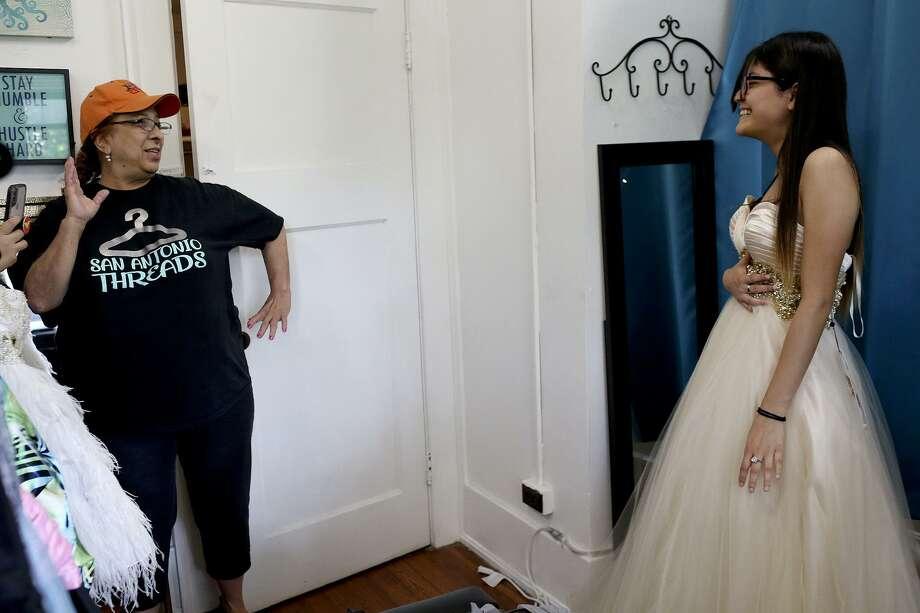 Volunteer Elida Rodriguez, left, tells Southside High School student Esperanza Ruiz, 17, to strike a pose after Ruiz decided on her prom dress at San Antonio Threads in San Antonio on Friday, May 11, 2018. Photo: Lisa Krantz / SAN ANTONIO EXPRESS-NEWS / SAN ANTONIO EXPRESS-NEWS