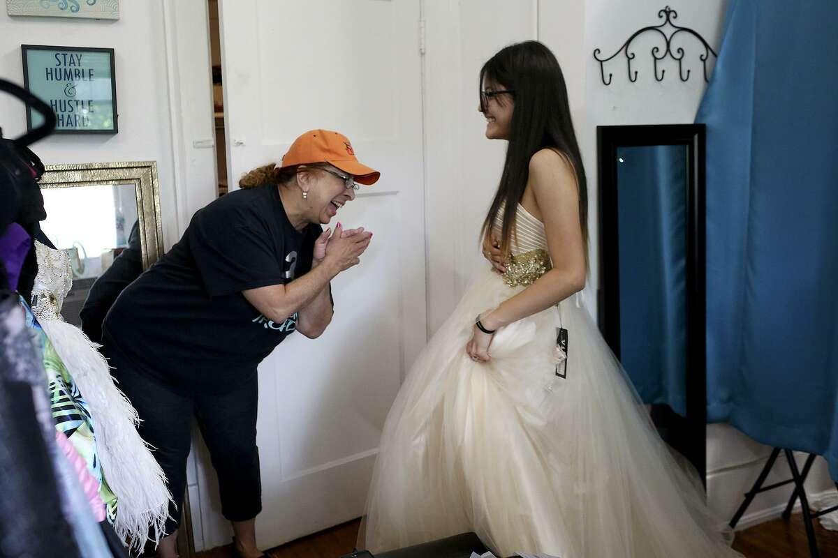 Volunteer Elida Rodriguez, left, laughs with Southside High School student Esperanza Ruiz, 17, after Ruiz decided on her prom dress at San Antonio Threads in San Antonio on Friday, May 11, 2018.