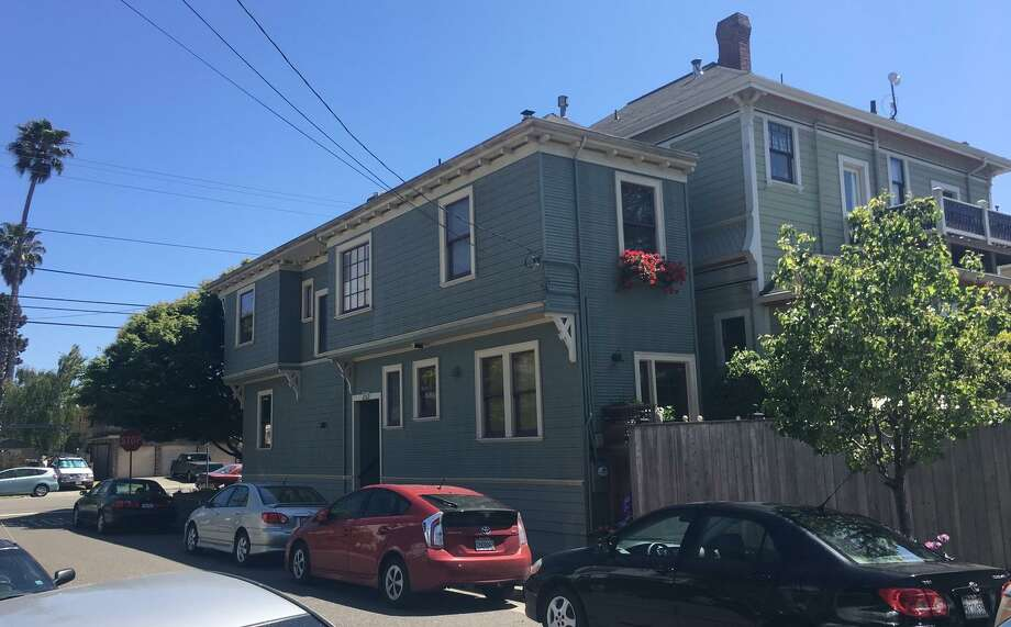 The spite house in Alameda is a two-story Colonial Revival that's only 12 feet wide at its broadest point and blocks several windows of the neighboring Queen Anne Victorian. Photo: Claire Sumalinog