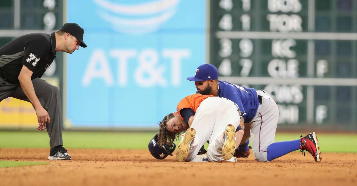 Umpire Jordan Baker (71) gets ready to call Houston Astros right fielder Josh Reddick (22) safe after a tag by Texas Rangers second baseman Rougned Odor (12) during action at Minute Maid Park Friday, May 11, 2018, in Houston. ( Steve Gonzales / Houston Chronicle )