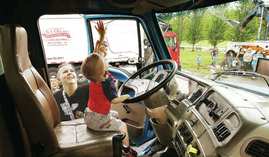 Emily Vandygriff helps her son, Cloud, 2, reach up to grab the rope controlling the air horn inside the cab of an R.P. Lumber truck from Edwardsville at Big Truck Day in Godfrey. Photo:       John Badman | The Telegraph