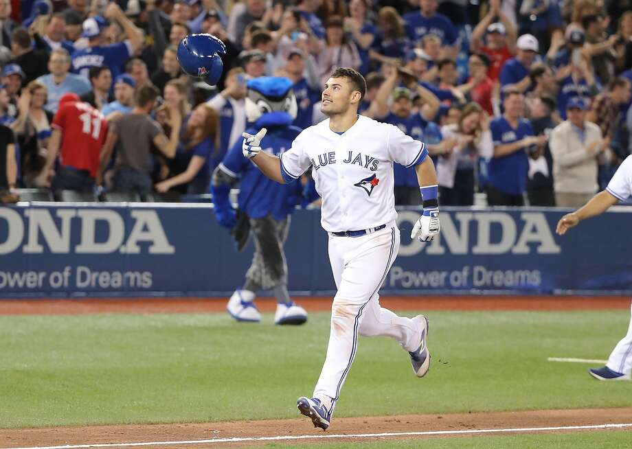 Toronto's Luke Maile tosses his helmet after his game-winning, two-run home run. Photo: Tom Szczerbowski / Getty Images