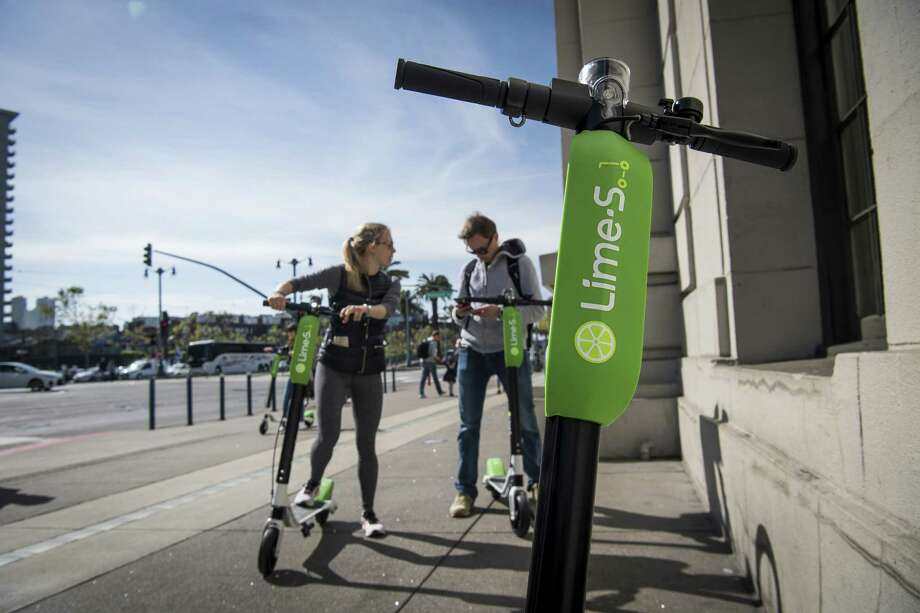 People use a smartphone to unlock Neutron Holdings Inc. LimeBike shared electric scooters in San Francisco on May 3, 2018. Photo: Bloomberg Photo By David Paul Morris. / © 2018 Bloomberg Finance LP