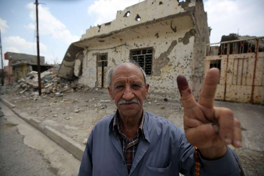 An Iraqi voter shows his ink-stained index finger in front of a damaged wall in western Mosul's Zanjili neighbourhood on May 12, 2018, still partially in ruins from the devastating months-long fight to oust the Islamic State (IS) group. Iraq began voting in its first parliamentary election since declaring victory over the Islamic State group, with the country hoping to shore up a fragile peace and rebuild. Polling stations opened around the conflict-scarred nation under tight security as  jihadists still pose a major security threat despite a sharp fall in violence. / AFP PHOTO / AHMAD AL-RUBAYEAHMAD AL-RUBAYE/AFP/Getty Images Photo: AHMAD AL-RUBAYE;Ahmad Al-rubaye / AFP / Getty Images