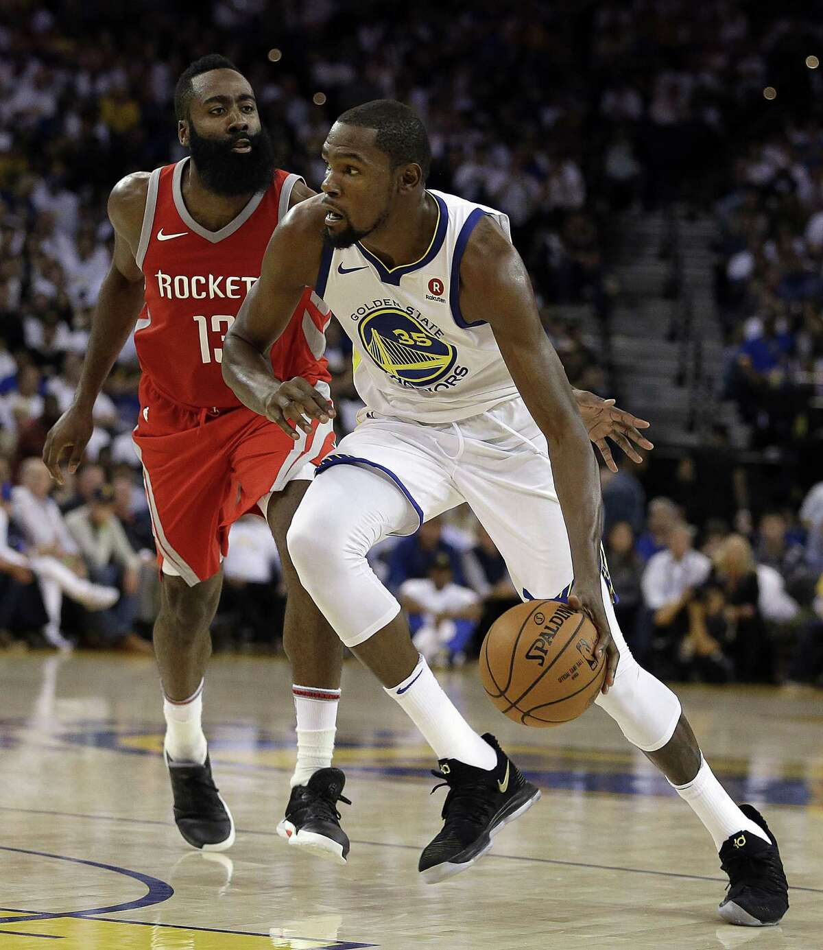 Golden State Warriors' Kevin Durant, right, drives the ball against Houston Rockets' James Harden in 2017.