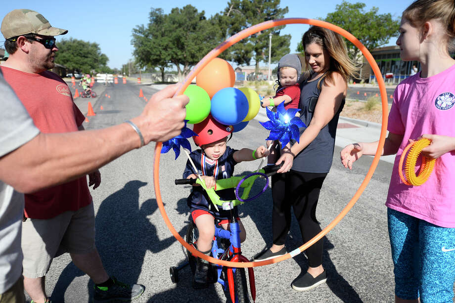 Bentley Butts, age 3, throws rings through a hoop while riding his bike during the Midland Children's Rehab Center annual Basin Bikefest May 12, 2018. James Durbin/Reporter-Telegram Photo: James Durbin