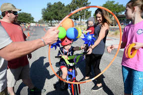 Bentley Butts, age 3, throws rings through a hoop while riding his bike during the Midland Children's Rehab Center annual Basin Bikefest May 12, 2018. James Durbin/Reporter-Telegram