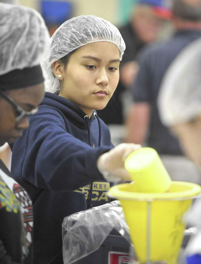 Melinda Sangthet, from Danbury High School, adds soy to a package of rice & soy meals. Students from Brookfield, Danbury and Abbott Technical high schools partnered to raise money to send food to those in need in Haiti. They met at the Congregational Church in Brookfield, Conn, to make pre-packaged meals on Saturday, May 12, 2018. Photo: H John Voorhees III / Hearst Connecticut Media / The News-Times