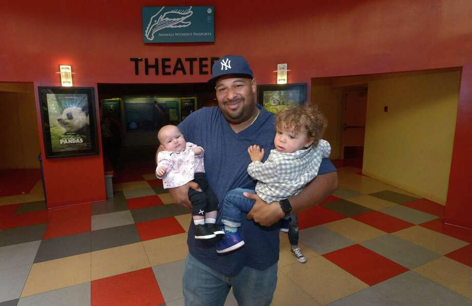 Visitors to the Maritime Aquarium including Stev Campbell and his kids, Mason, 4 months, and Mia, 2, exit the IMAX theater Friday, May 11, 2018, in Norwalk, Conn. The Connecticut Department of Transportation has put $34.5 million on the table for The Maritime Aquarium at Norwalk to replace the IMAX Theater and build new exhibit space necessitated by the upcoming replacement of the Walk Bridge. Photo: Erik Trautmann / Hearst Connecticut Media / Norwalk Hour