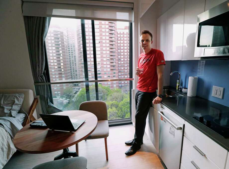 In this May 1, 2018, photo, Carmel Place resident Matthew Alexander poses for a photo in the kitchen, dining room, office space and bedroom of his small co-living studio apartment in New York. Alexander says after years of sharing spaces with roommates, he likes the independent, minimalist living style of the building, which features amenities such as housekeeping, grocery delivery, dry-cleaning pickup, a rooftop terrace, a gym, and social gatherings. (AP Photo/Kathy Willens) Photo: Kathy Willens / Copyright 2018 The Associated Press. All rights reserved.
