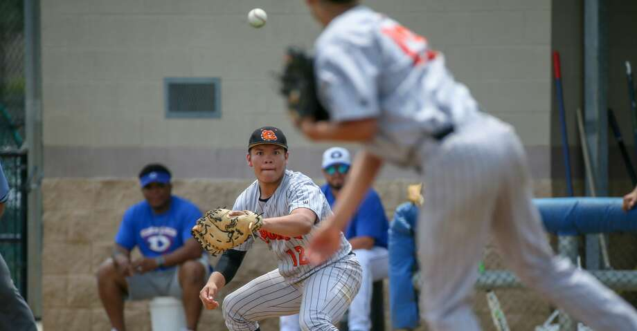 May 12, 2018:  La Porte Bulldogs Dylan Conde throws the ball to La Porte Bulldogs Mark Gomez and gets an out on Dickinson Gators Kam Johnson in the bottom of the first inning of the high school baseball playoff game between the La Porte Bulldogs and Dickinson Gators in Dickinson, Texas.  (Leslie Plaza Johnson/Freelance Photo: Leslie Plaza Johnson/For The Chronicle