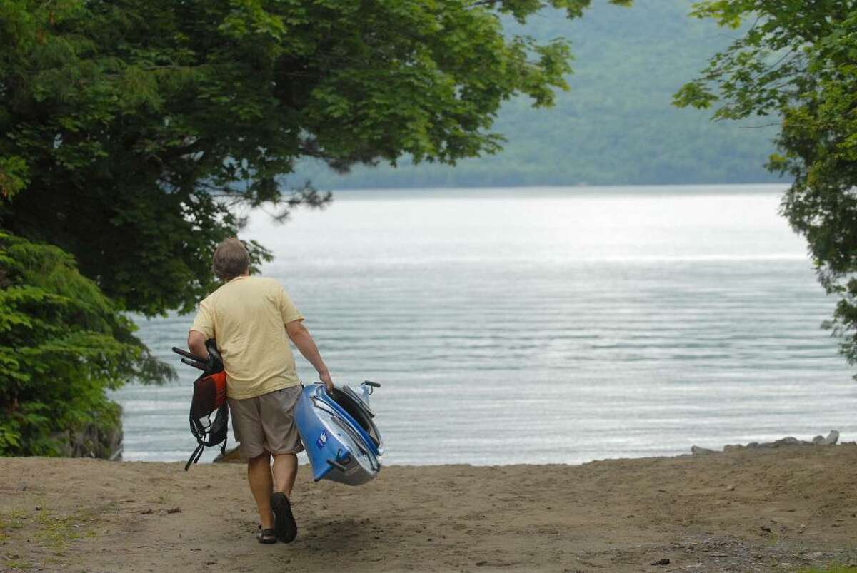 Chris Navitsky, the Lake George Waterkeeper, carries his kayak to the water's edge on Lake George in the town of Bolton Landing. He says life preserver use is essential. (Paul Buckowski / Times Union)