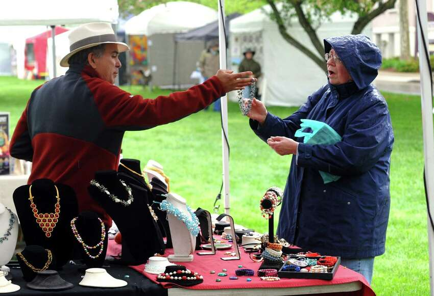Antoinette Penkala looks at jewelry created by Jaime Blanch, who runs Pearl Shop from Watertown, MA at the annual Mother's Day Artisan Fair on the historic green in downtown Milford, Conn., on Saturday, May 12, 2018. The event featured as many as 100 artists offering handcrafted items, photography, jewelry and fine art as well as handcrafted apparel and food vendors. The market continues on Sunday from 11 a.m. - 4 p.m.