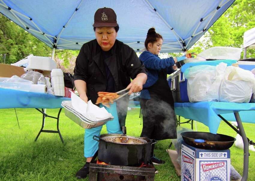 Phon Ketkeo operates Thai Kitchen for hungry customers at the annual Mother's Day Artisan Fair on the historic green in downtown Milford, Conn., on Saturday, May 12, 2018. The event featured as many as 100 artists offering handcrafted items, photography, jewelry and fine art as well as handcrafted apparel and food vendors. The market continues on Sunday from 11 a.m. - 4 p.m.