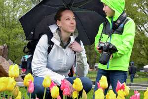 Shauna Salter of Pittsfield accompanies her son Logan, 6, as he photographs the flower beds during the 70th Annual Tulip Festival in Washington Park Saturday. Salter was among many moms who came to the festival on the day before Mother's Day. The event continues Sunday with more festivities, including a recognition of some of the region's outstanding moms. The big day's weather will be an improvement over Saturday's rains and cool temperatures, with a 72-degree high and partly cloudy skies predicted. (John Carl D'Annibale/Times Union)