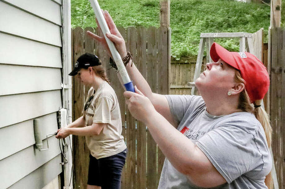 Members of the Junior League of Greater Alton paint the the home of Diana Kay in the 3600 block of Horn Avenue in Alton Saturday during the annual Bucket Brigade effort.