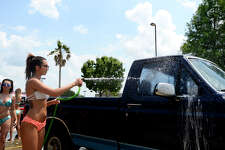 Twin Peaks employee Seana Norman washes a car during a charity car wash at the restaurant on Saturday, May 12. The car wash raised funds for Folds of Honor, a charity that provides scholarships to children and spouses of fallen and disabled members of the military.  Photo taken Saturday 5/12/18 Ryan Pelham/The Enterprise