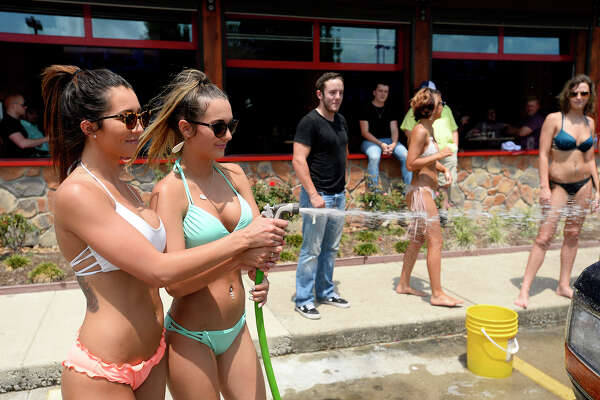 Twin Peaks employees Shelby Norman and Ally Joubert during a charity car wash at the restaurant on Saturday, May 12. The car wash raised funds for Folds of Honor, a charity that provides scholarships to children and spouses of fallen and disabled members of the military.  Photo taken Saturday 5/12/18 Ryan Pelham/The Enterprise