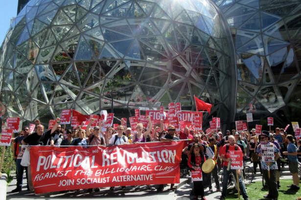 Housing advocates call for a Seattle 'head tax' in front of Amazon's iconic Spheres.