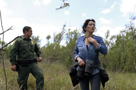 U.S. Border Patrol agent Marcelino Medina detains Veronica Reyes, 26, of Veracruz, Mexico, near the Anzalduas International Bridge in Mission, Texas, Thursday, May 10, 2018. Reyes was with a group of five immigrants attempting to enter the U.S. illegally. The rest were able to cross back into Mexico and escape detention.