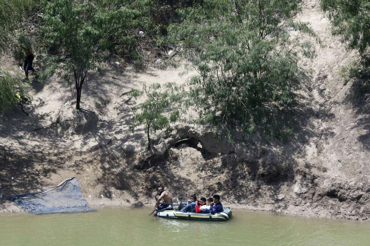 A smuggler prepares to take a group of migrants across the Rio Grande in Reynosa, Mexico. They were being taken to a site on the U.S. side in Hidalgo County.