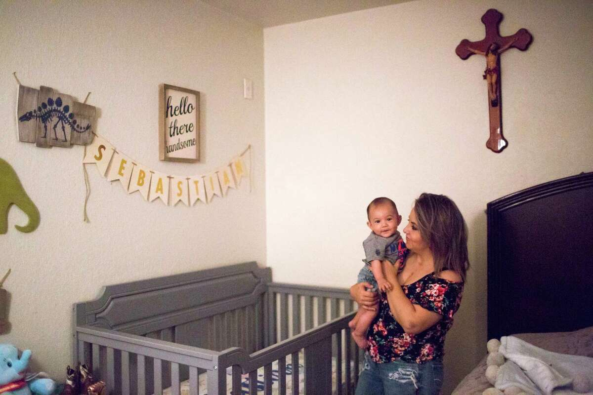 Cecilia Figueroa, 31, picks up her son Sebastian Figueroa from his crib before breakfast, Wednesday, May 9, 2018, at their home in Port Arthur. While being pregnant with Sebastian, Cecilia was told that she need it to end her pregnancy because of a potentially fatal heart condition but instead a team of doctors at UTHealth performed a minimally invasive procedure known as transcatheter aortic valve replacement (TAVR) so she could continue her pregnancy.