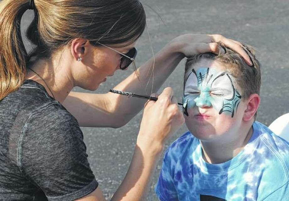 TJ Weis, 9, the son of Tim and Stephanie Weis of Quincy, gets his face painted by Emilee Monkman on Saturday at the Illinois College Osage Orange Festival. Photo:       Samantha McDaniel-Ogletree | Journal-Courier