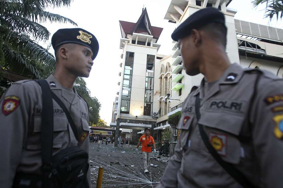 Officers patrol the site of one of three suicide bomb attacks on Christian churches in the city of Surabaya. Photo: Trisnadi