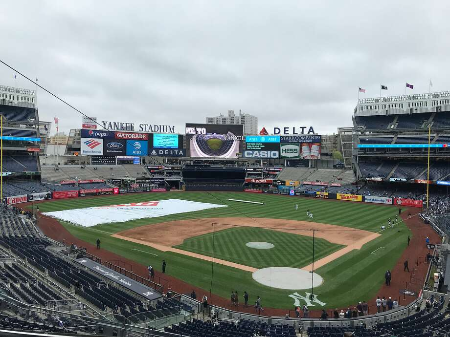 Dark skies threaten rain and the tarp is ready to be rolled out at Yankee Stadium on Sunday morning. Photo: Susan Slusser/The Chronicle