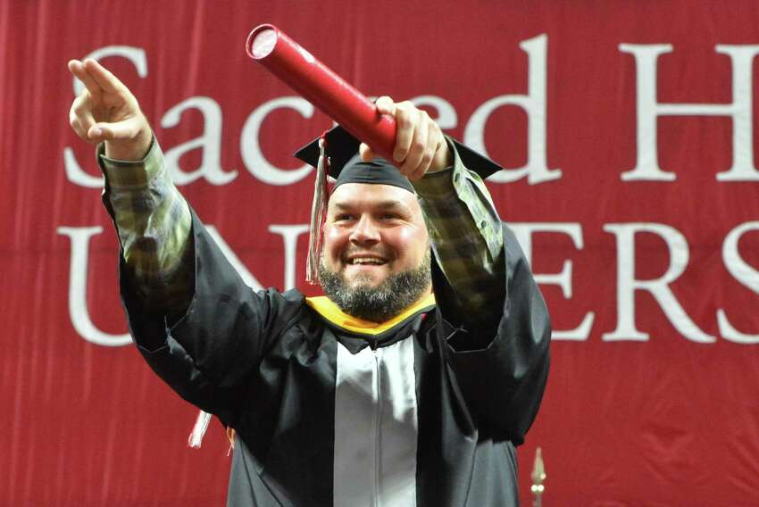 Trumbull's Mark Robitzek points to the crowd as he gets his diploma and a B.S in Finance during the Sacred Heart University Graduation Ceremony on Sunday May 13, 2018 at Webster bank Arena in Bridgeport Conn.