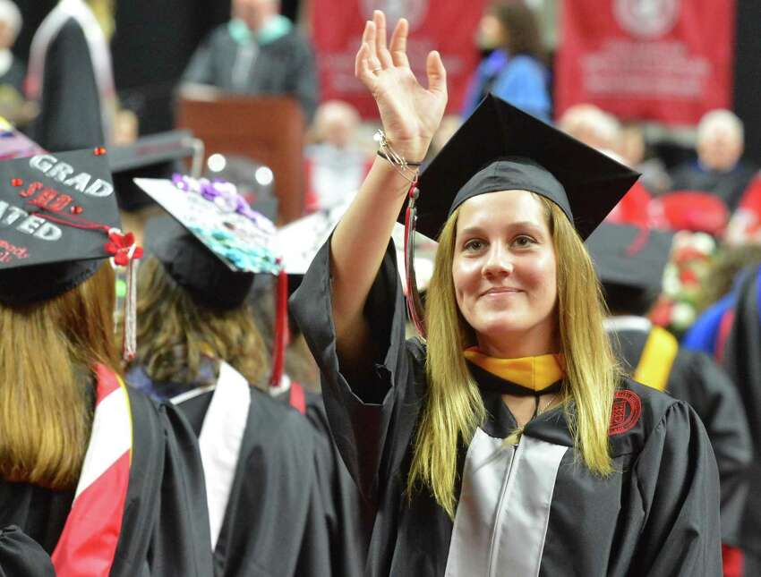 Shelton's Shalyn Stevens waves with diploma in hand during the Sacred Heart University Graduation Ceremony on Sunday May 13, 2018 at Webster Bank Arena in Bridgeport Conn.