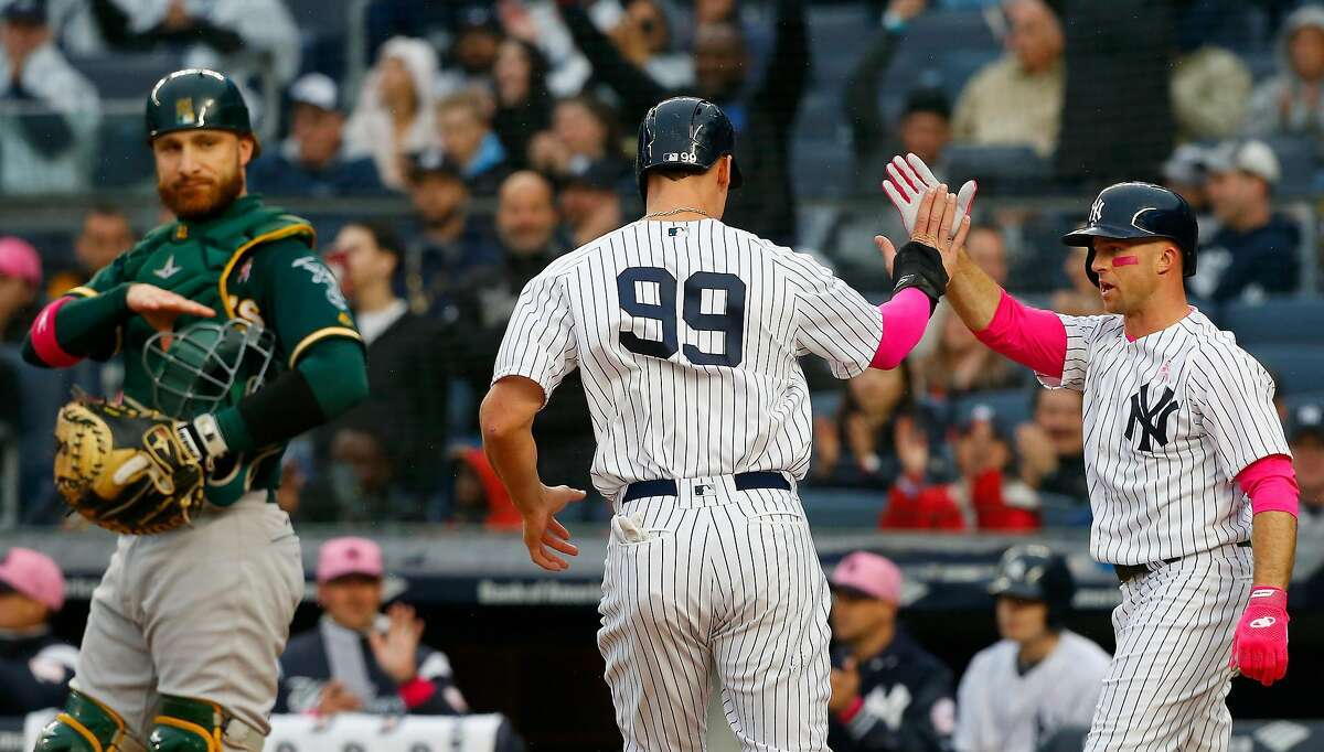 NEW YORK, NY - MAY 13: Jonathan Lucroy #21 of the Oakland Athletics looks on as Aaron Judge #99 and Brett Gardner #11 of the New York Yankees celebrate after both scored in the first inning at Yankee Stadium on May 13, 2018 in the Bronx borough of New York City. (Photo by Jim McIsaac/Getty Images)
