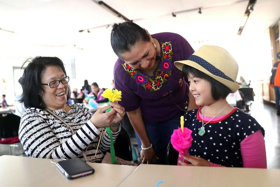 Irma Ortiz (center) instructs Wendy Pan of San Jose and her daughter, Hayden, 10, in a Mother's Day paper flower making workshop at the Exploratorium in San Francisco. Photo: Scott Strazzante / The Chronicle