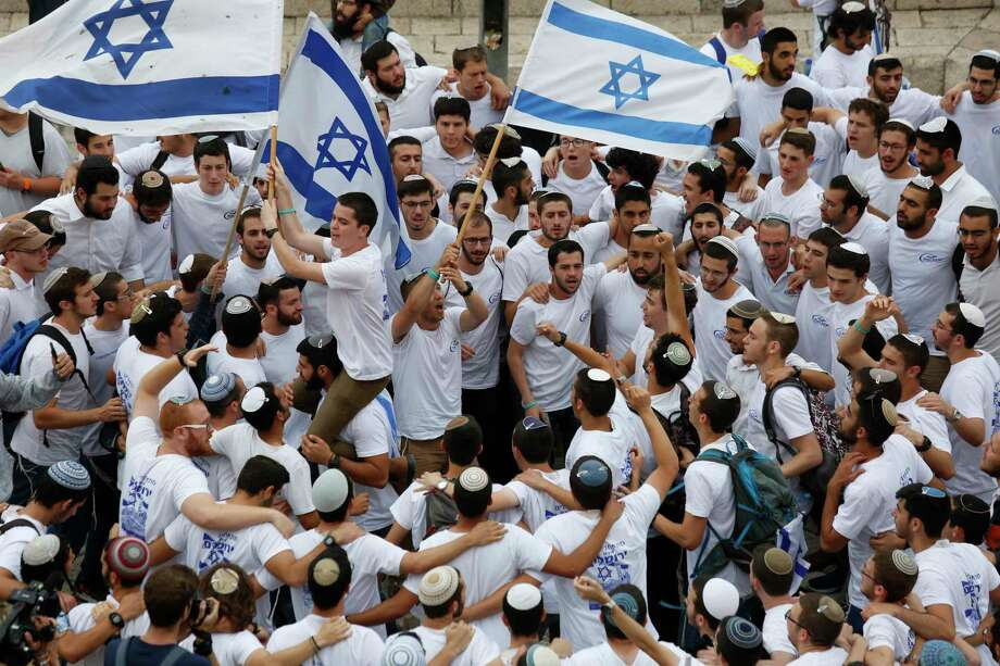 Israeli youths wave national flags outside the Old City's Damascus Gate, in Jerusalem, Sunday, May 13, 2018. Israel is marking the 51st anniversary of its capture of east Jerusalem in the 1967 Middle East war. (AP Photo/Ariel Schalit) Photo: Ariel Schalit / Copyright 2018 The Associated Press. All rights reserved.