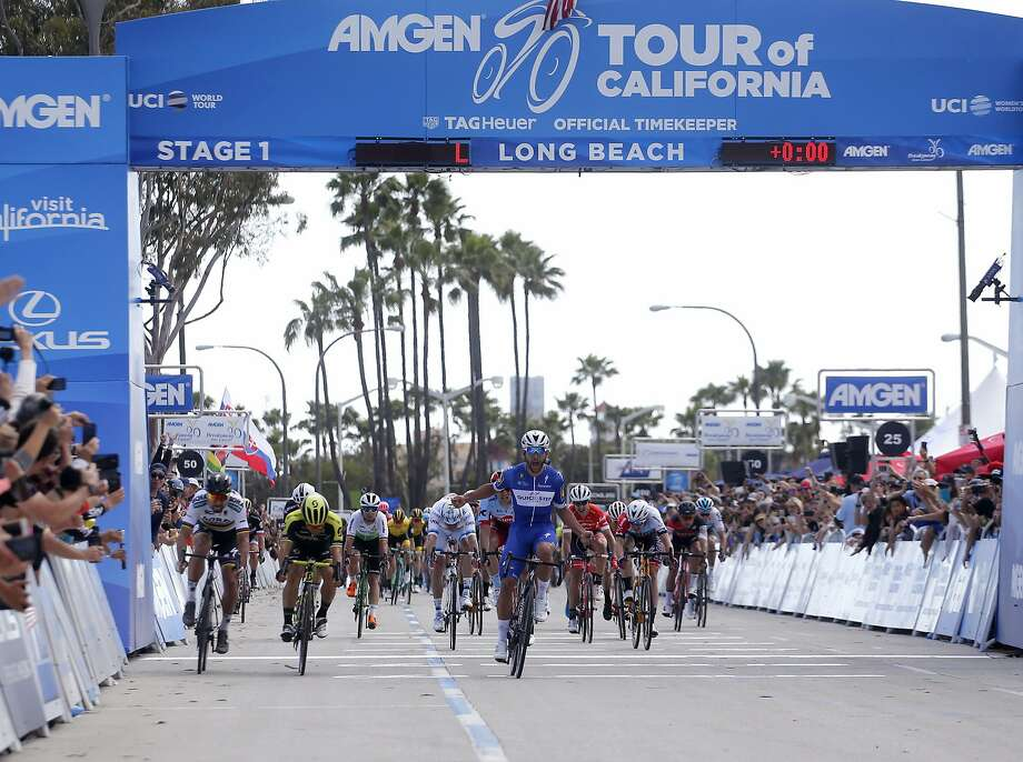 Colombia's Fernando Gaviria (center) crosses the finish line in Long Beach first to take Sunday's first stage of the Tour of California. Photo: Ringo H.W. Chiu / Associated Press