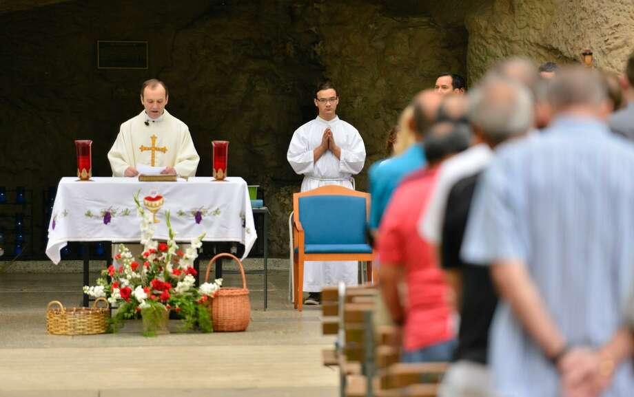 Father Leo Perez leads prayers during a Mother's Day Mass at Our Lady of Lourdes Grotto on Sunday morning. Photo: Robin Jerstad /For The San Antonio Express-News