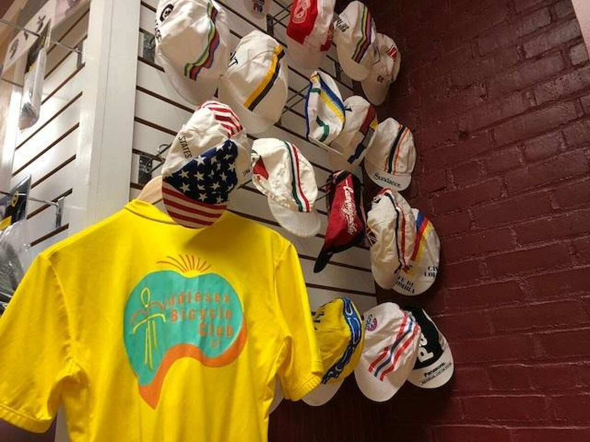 Cycling caps and a Middlesex Bicyling Club tee donated by Andy Raymond form a display on the upper level inside Pedal Power on Main Street.